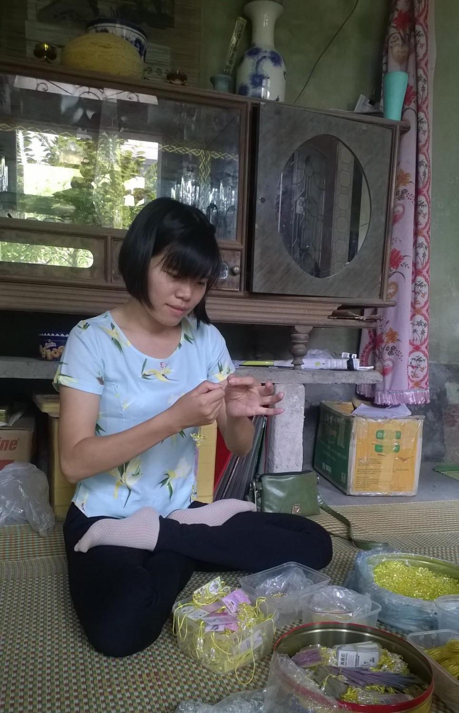 Nguyet fazendo flores de lótus, flor símbolo do Falun Dafa (Dang Thi Nguyet)