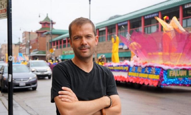 Christopher Stoltez viu o desfile do Falun Dafa Parade quando passava pela Wentworth Avenue, no bairro chinês de Chicago, em 21 de julho (Stacey Tang/Epoch Times)