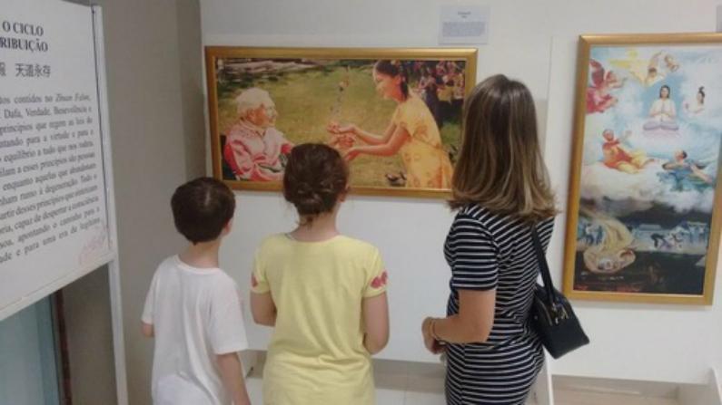 Uma mãe e seus filhos apreciam as obras de arte