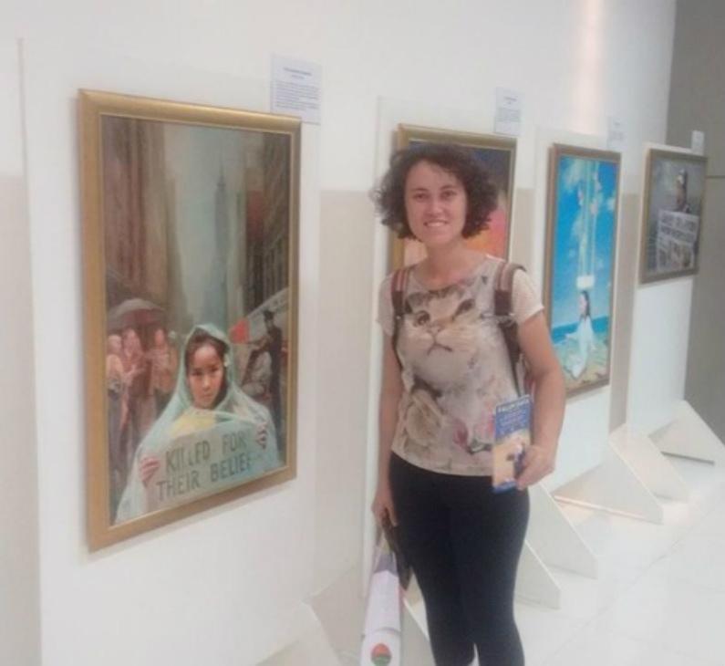 Carolina, uma artista, em frente a sua pintura favorita (Minghui.org)