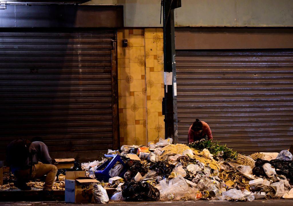 Pessoas procuram comida no lixo em uma rua vazia de Caracas, em 23 de outubro de 2018. Quando o sol se põe, a solidão reina nas ruas de Caracas, castigada pelo crime desenfreado e pela crise econômica. Segundo as ONGs, na Venezuela ocorreram cerca de 26 mil mortes violentas em 2017, com uma taxa de 89 para cada 100 mil habitantes, 15 vezes superior à média mundial (Ronaldo Schemidt/AFP/Getty Images)