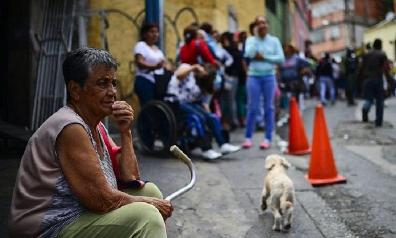Idosa enfrenta fila para comprar alimentos básicos e utensílios domésticos do lado de fora de um supermercado no bairro pobre de Lidice, em Caracas, Venezuela, em 27 de maio de 2016 (Ronaldo Schemidt/AFP/Getty Images)