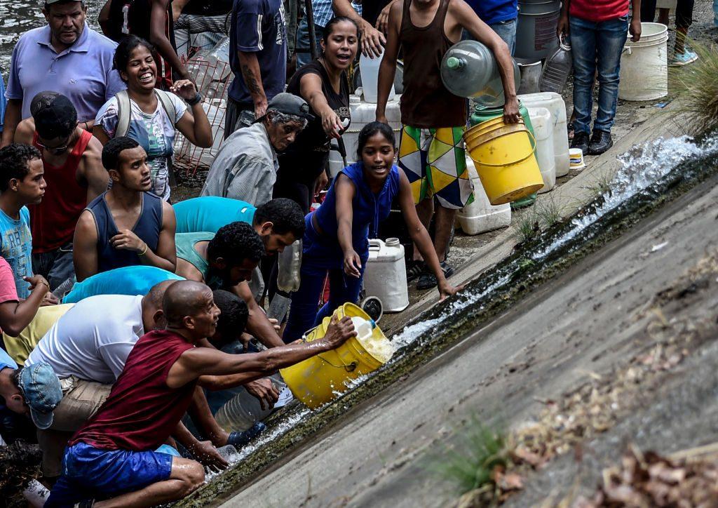 Pessoas coletam água de um canal de esgoto no rio Guaire, em Caracas, em 11 de março de 2019, enquanto um blecaute em massa continua afetando algumas áreas do país (JUAN BARRETO / AFP / Getty Images)
