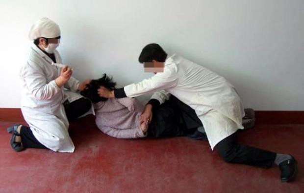 Reconstituição mostra uma mulher saudável sendo injetada à força com drogas psiquiátricas (Minghui.org)