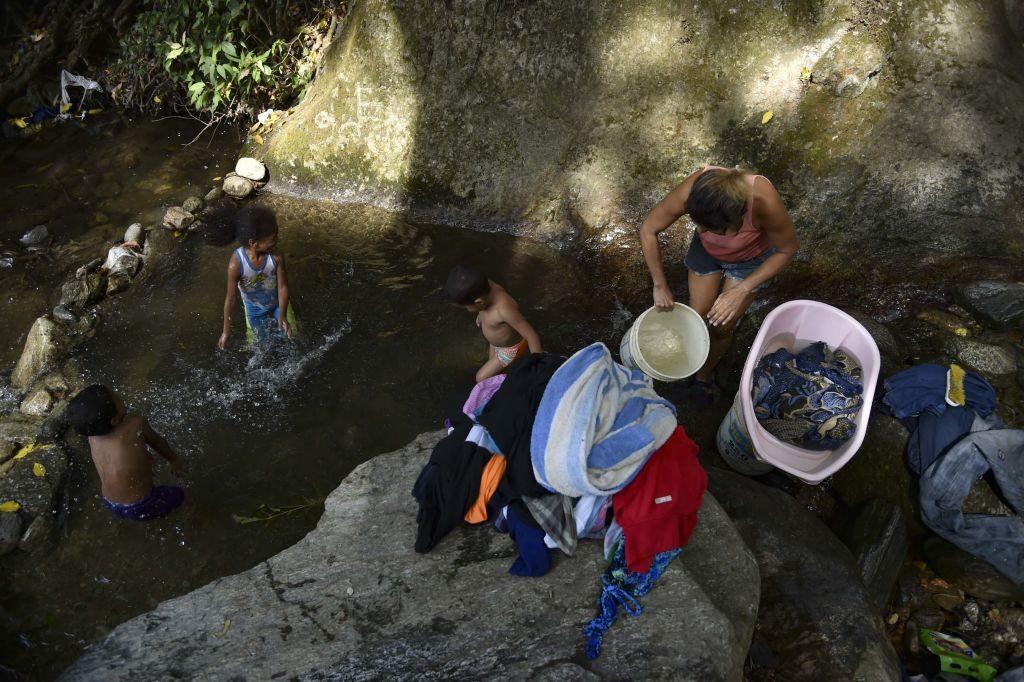 Mulher lava roupas em um riacho que desce do morro El Ávila, em Caracas, em 2 de abril de 2019. O país foi afetado por uma série de apagões devastadores que deixaram milhões de pessoas sem água (YURI CORTEZ / AFP / Getty Images)