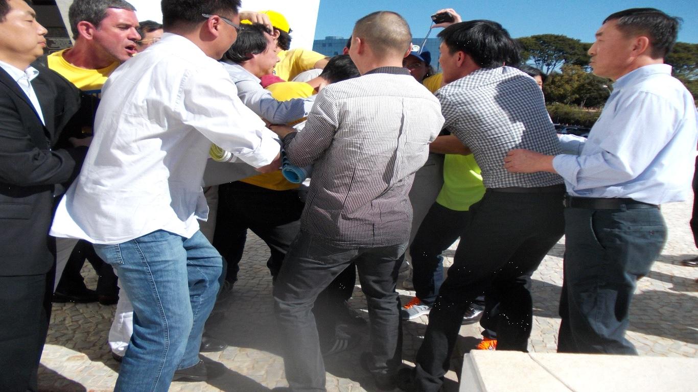 Praticantes de Falun Gong, incluindo mulheres, foram atacados em Brasília pelos agentes da comitiva chinesa com socos, pontapés e estrangulamento. No dia anterior, os praticantes foram cercados por vans da comitiva chinesa, fotografados e filmados pelos seguranças e agentes chineses (Epoch Times)