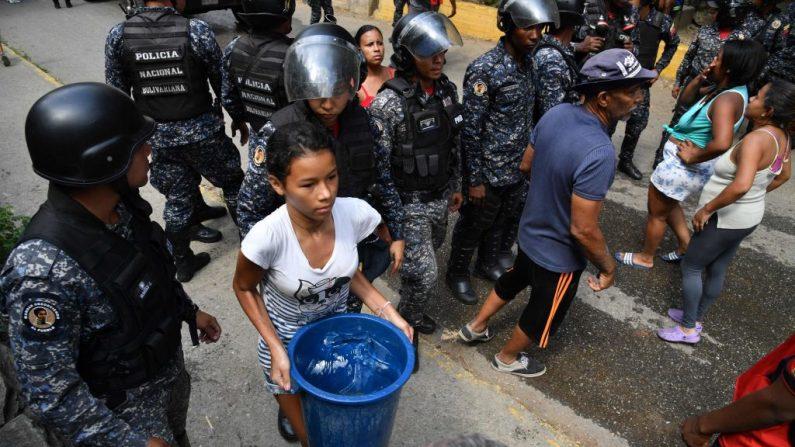 Membros da Polícia Nacional Bolivariana organizam a distribuição de água potável para os moradores do bairro de San Agustín, em Caracas, em 11 de março de 2019, em meio a um blecaute maciço que afetou a Venezuela socialista (YURI CORTEZ / AFP / Getty Images)