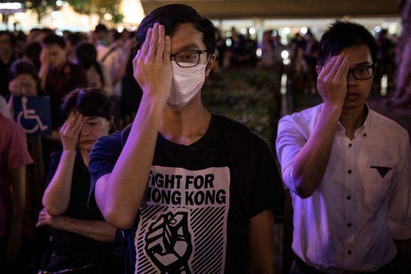 Manifestantes cobrem os olhos esquerdos e permanecem em silêncio durante a 74a Assembléia do Aniversário da Libertação de Hong Kong, em 30 de agosto de 2019 (Chris McGrath / Getty Images)