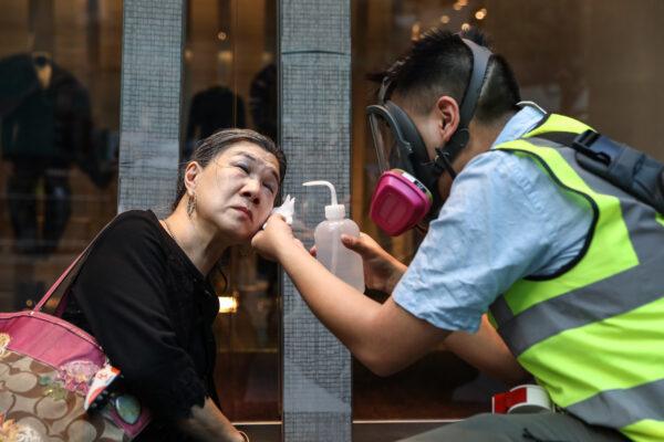 Uma mulher é tratada depois que a polícia disparou gás lacrimogêneo para dispersar manifestantes no distrito central de Hong Kong em 12 de novembro de 2019 (Dale De La Rey / AFP via Getty Images)