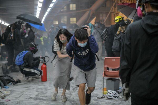 Manifestantes correm para se esconder depois que a polícia de choque disparou gás lacrimogêneo em direção à ponte que eles tentavam subir para escapar do campus da Universidade Politécnica de Hong Kong e da polícia, no distrito de Hung Hom, em Hong Kong, em 18 de novembro de 2019 ( Anthony Wallace / AFP via Getty Images)
