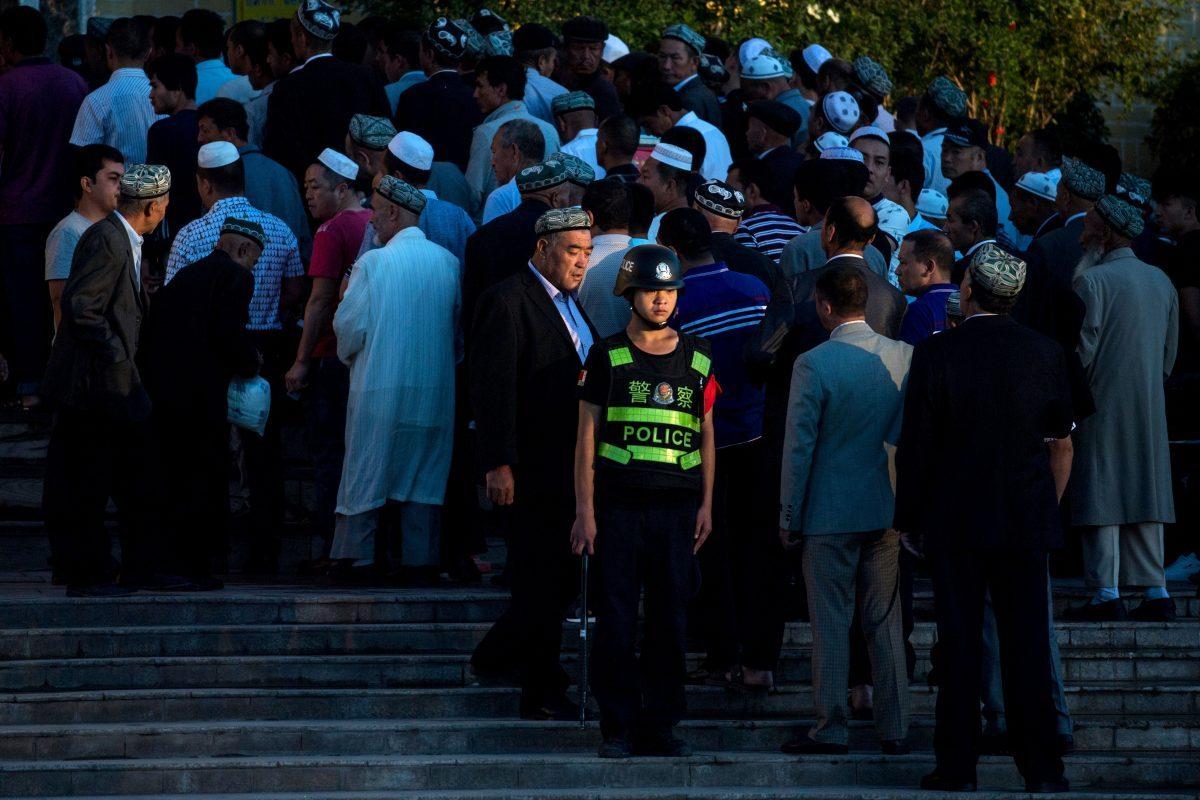 Um policial em serviço enquanto muçulmanos chegam à oração matinal de Eid al-Fitr na mesquita Id Kah em Kashgar, Xinjiang, China, em 26 de junho de 2017 (Johannes Eisele / AFP / Getty Images)