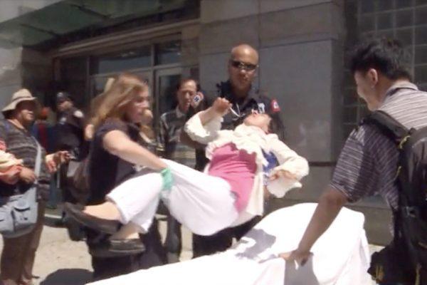 Fu Yuxia foi transferida para uma ambulância após ser agredida enquanto protestava contra a perseguição do PCC ao Falun Gong, fora do consulado chinês em Nova Iorque em 1º de julho de 2014 (NTD Television)