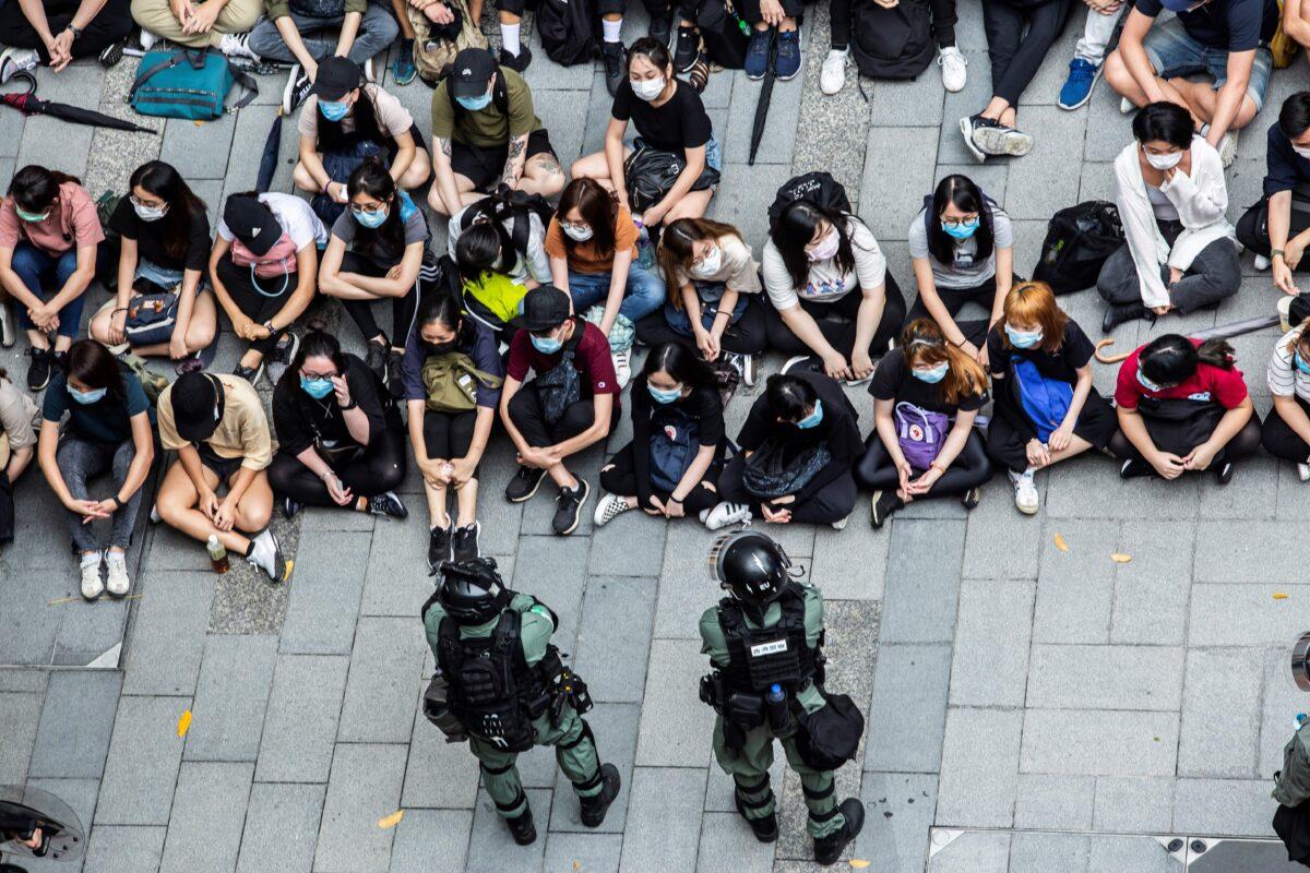 A polícia de choque deteve um grupo de pessoas durante um protesto no distrito de Causeway Bay, em Hong Kong, em 27 de maio de 2020, enquanto a legislatura da cidade debate uma lei que proíbe insultar o hino nacional da China (Isaac Lawrence / AFP via Getty Images)