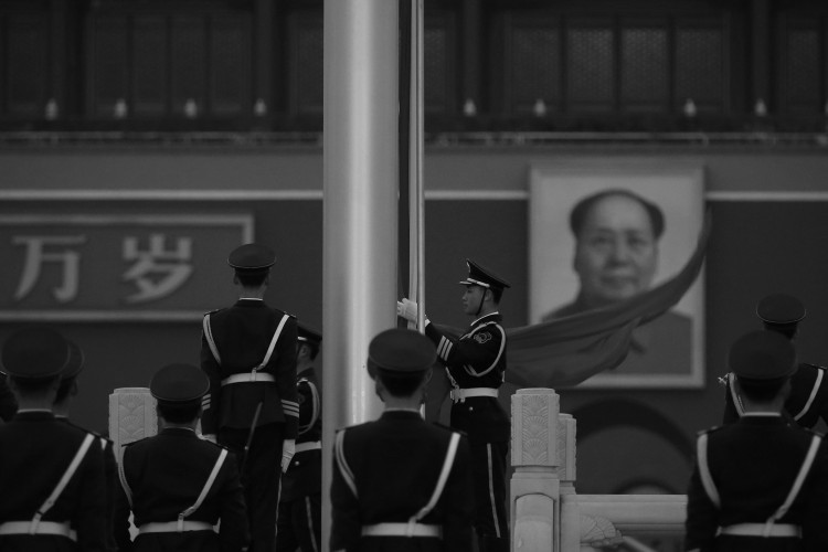 Um oficial da polícia paramilitar recolhe a bandeira da República Popular da China na frente do retrato de Mao Tsé-Tung pendurado na Praça da Paz Celestial, em Pequim no dia 2 de março. A Televisão Central da China recentemente citou o pronunciamento de Mao de que estava disposto a ver centenas de milhões de chineses assassinados (Feng Li/Getty Images)