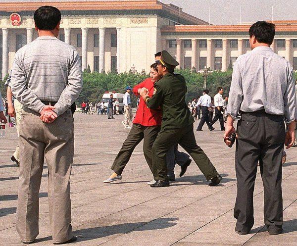 Policiais à paisana observam uma praticante do Falun Gong levada à força pela polícia para uma van da polícia na Praça Tiananmen, em Pequim,em 11 de maio de 2000 (STEPHEN SHAVER / AFP via Getty Images)