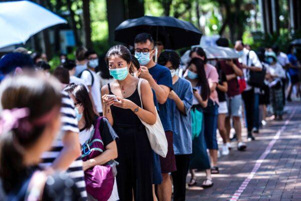 Uma mulher usa seu telefone enquanto espera para votar durante as eleições primárias em Hong Kong em 12 de julho de 2020 (Isaac Lawrence / AFP via Getty Images)
