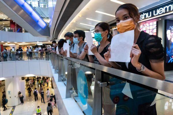 Manifestantes seguram papéis em branco durante uma manifestação em um shopping center de Hong Kong em 6 de julho de 2020. Os habitantes de Hong Kong estão encontrando maneiras criativas de expressar sua discordância quando a polícia começou a prender pessoas que exibiam slogans políticos que agora são proibidos (Billy H.C. Kwok / Getty Images)