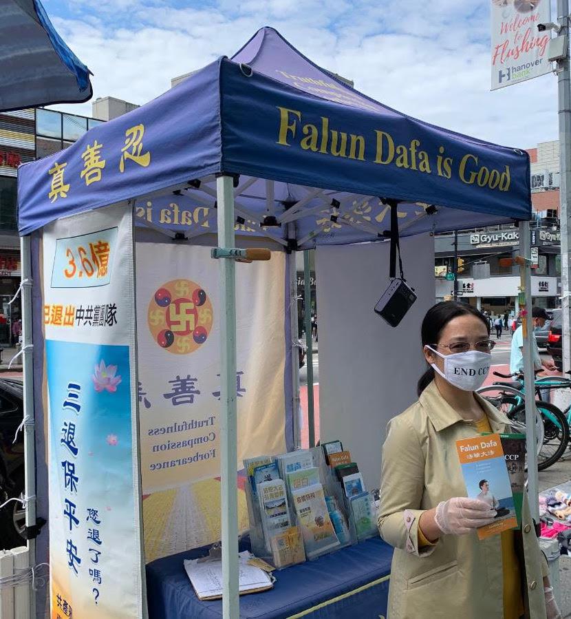 A praticante do Falun Gong Xiao Ping em frente a um estande relatando sobre a perseguição da prática espiritual na China em Flushing, Nova York, em 1º de outubro de 2020. (Cortesia do Epoch Times)