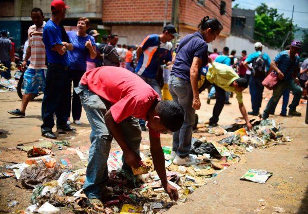 Pessoas procuram comida fora de um supermercado saqueado no bairro de El Valle, em Caracas, em 21 de abril de 2017 (RONALDO SCHEMIDT / AFP via Getty Images)