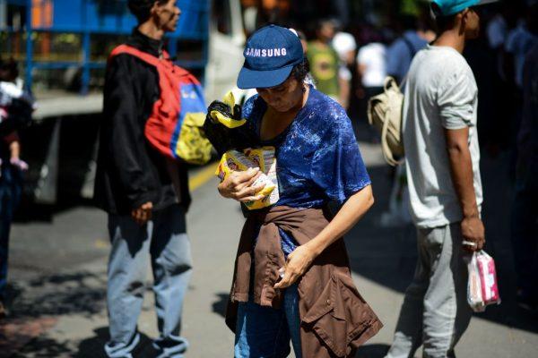 Mulher segura dois sacos de farinha após fazer fila em frente a um supermercado em Caracas (Venezuela) para comprar alimentos básicos e produtos domésticos em 10 de novembro de 2017 (FEDERICO PARRA / AFP via Getty Images)