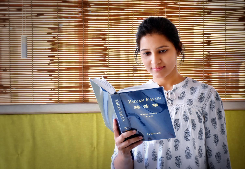 Prajakta lendo Zhuan Falun, o livro principal da práctica de Falun Dafa (Veeresh M. Honnihal)