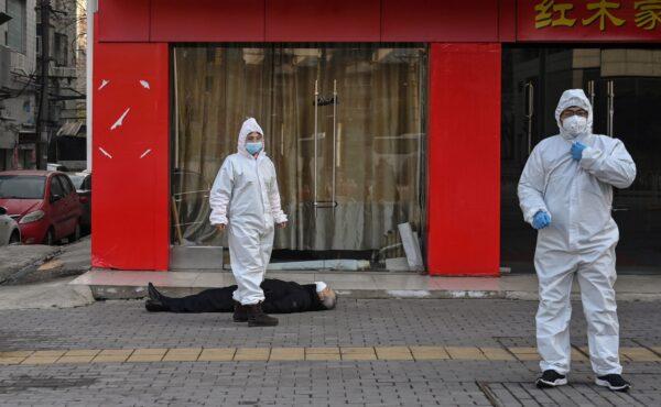 Autoridades chinesas em trajes de proteção revistam um idoso com máscara facial que desmaiou e morreu em uma rua perto de um hospital em Wuhan, China, em 30 de janeiro de 2020 (HECTOR RETAMAL / AFP via Getty Images)