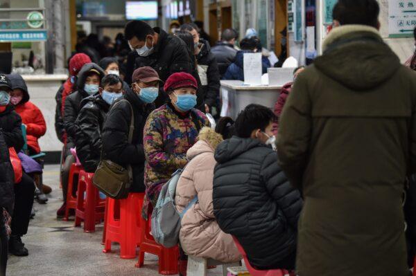 Pessoas usando máscaras enquanto esperam no Hospital da Cruz Vermelha de Wuhan em 24 de janeiro de 2020 (Hector Retamal / AFP via Getty Images)